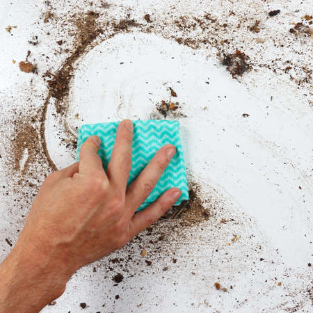 heavily: Hand with rag cleans the heavily dirty surface