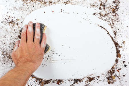 wiping: Hand with wet black sponge wiping a heavily dirty surface