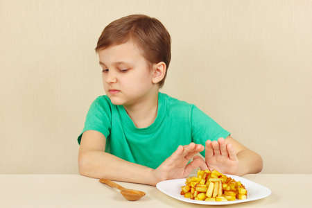 reluctance: Little cute boy refuses to eat a french fries