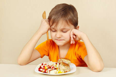 reluctance: Little disaffected boy does not want to eat a pasta with rissole