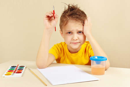 preoccupied: Little preoccupied artist in a yellow shirt is thinking what to paint Stock Photo