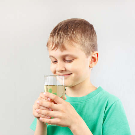 Little blonde boy with a glass of fresh lemonade Stock Photo