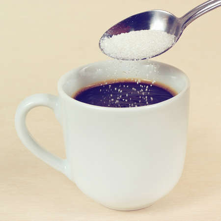 Sugar is poured from a spoon in a coffee cup, gently toned