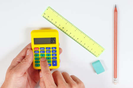 Hands calculate using a pocket digital calculator over a workplace of the engineer Stock Photo