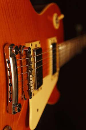 Vintage electric rock guitar closeup on the black background. Selective focus. Stock Photo