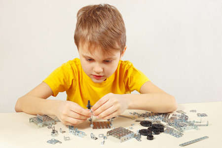 Young engineer plays with mechanical starter kit at the table Stock Photo