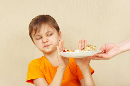 reluctance: Little displeased boy refuses to eat a pasta with cutlet Stock Photo