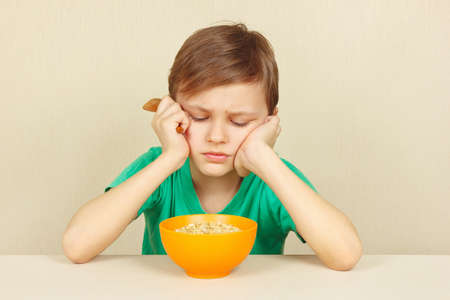 reluctance: Little discontented boy does not want to eat a porridge Stock Photo