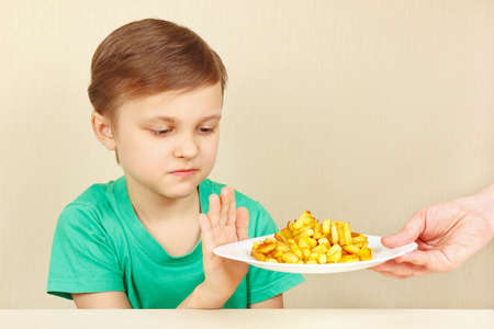 reluctance: Little cute unhappy boy refuses to eat a fried potatoes Stock Photo