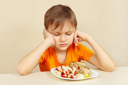 reluctance: Little displeased boy does not want to eat a pasta with rissole Stock Photo