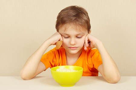 Little unhappy boy does not want to eat a porridge