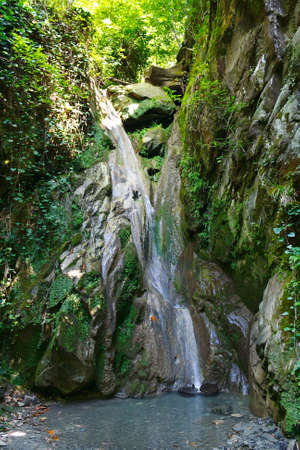 Beautiful refreshing waterfall among the rocks in a mountain forest Stock Photo