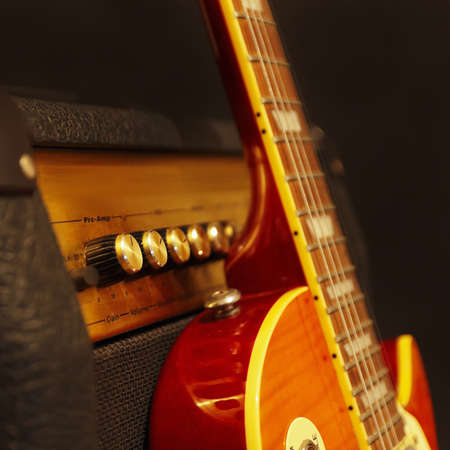Electric guitar with amplifier on the black background. Shallow depth of field, low key, close up.