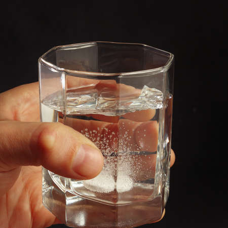 fizzy tablet: Hand with a glass of water and soluble tablet on a dark background.