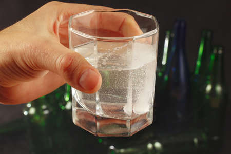 effervescence: Hand with a glass of water and soluble tablet of a hangover on a dark background.