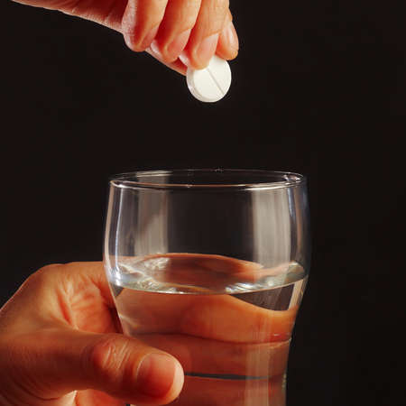 effervescence: Hand with a soluble tablet over the glass of water on a black background. Stock Photo