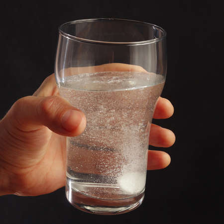 effervescence: Hand with a glass of water and effervescent pill on a dark background. Stock Photo