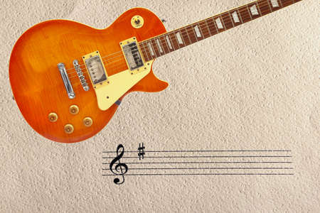 Stave and honey sunburst vintage electric guitar at the top of the rough cardboard background.