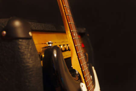 amp: Classic electric guitar with combo amplifier on the black background. Shallow depth of field, low key, close up.