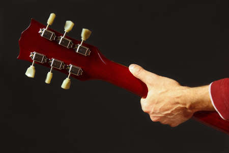 Hands of musician behind the guitar neck on a dark background Stock Photo