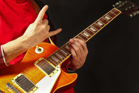 Hands of rock guitarist playing the electric guitar on a dark background