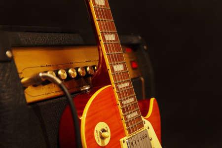 黒の背景にコンボ ・ アンプとエレキギター。低いキーは、フィールドの浅い深さをクローズ アップ。