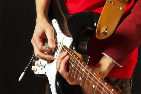 Posing hands of rock guitarist playing the electric guitar on the black background