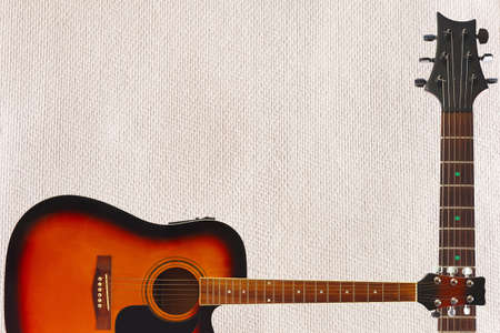 Acoustic jumbo guitar and neck on the cardboard background, with plenty of copy space.
