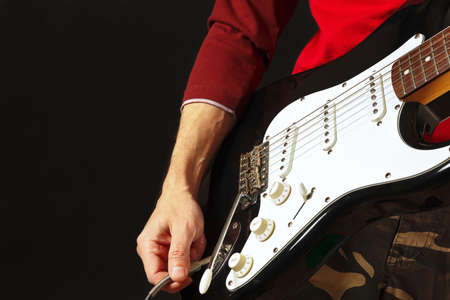Hand inserts input jack to electric guitar on the black background.