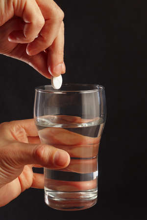 effervescence: Hand with an effervescent tablet from headache over the glass of water on a black background.