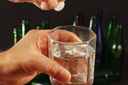 dissolve: Hand with an effervescent pill from hangover over a glass of water on a dark background.