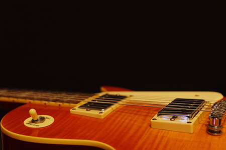 Honey sunburst vintage electric blues guitar closeup on the black background, with plenty of copy space. Selective focus. Stock Photo