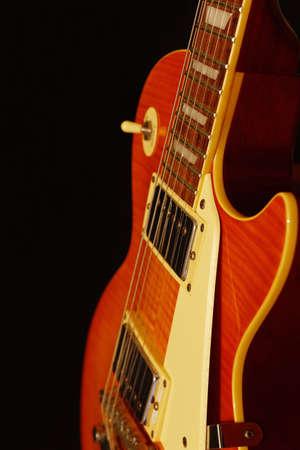 Honey sunburst vintage electric rock guitar closeup on the black background. Shallow depth of field.