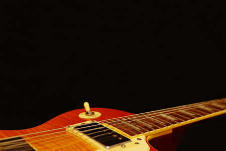 Vintage electric blues guitar closeup on the black background, with plenty of copy space. Selective focus. Stock Photo
