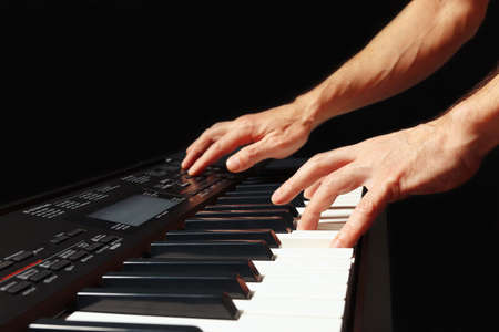 Hands of musician playing the digital piano on a black background