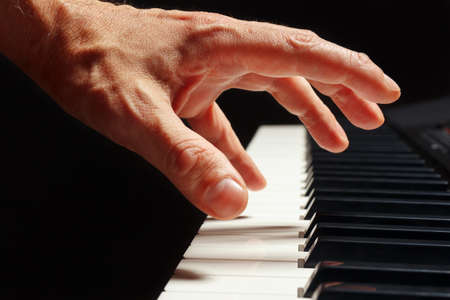 Hand of pianist play the keys of the electronic piano on a black background close up Stock Photo