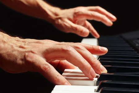 Hands of pianist play the keys of the piano on a black background close up