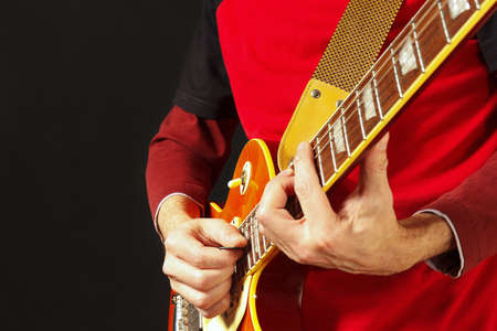 Guitarist playing the electric guitar on a dark background Stock Photo