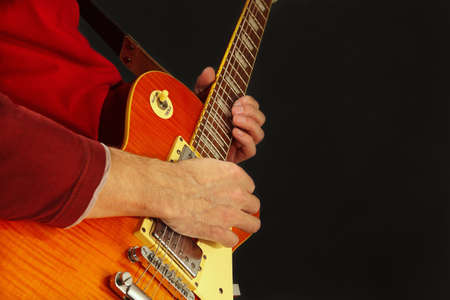 Posing hands of the artist playing the electric guitar on a dark background