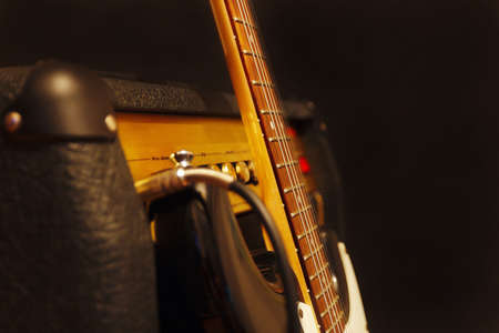 Classic electric guitar with amplifier on the black background. Shallow depth of field, low key, close up.