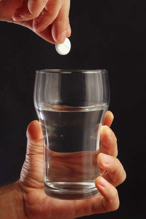Hand with an effervescent pill from headache over the glass of water on a black background.