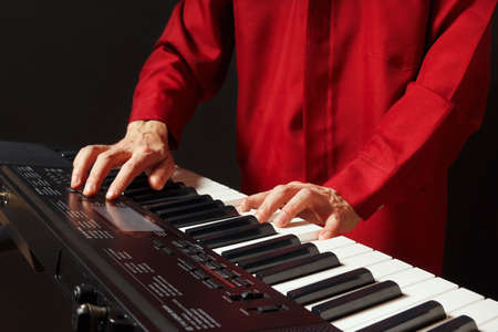 Pianist playing the electronic organ on a black background