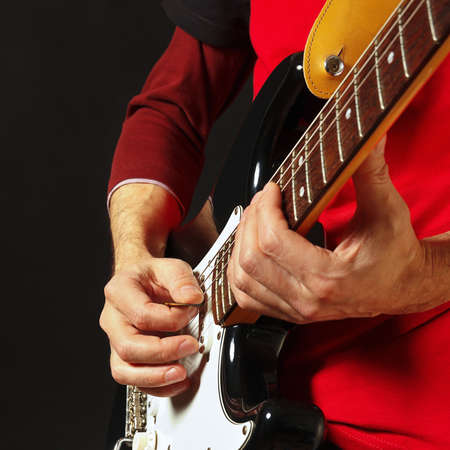 Artist with electric guitar on the black background Stock Photo