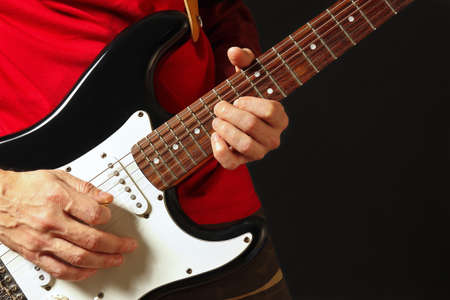 Musician put fingers for chords on electric guitar on the black background