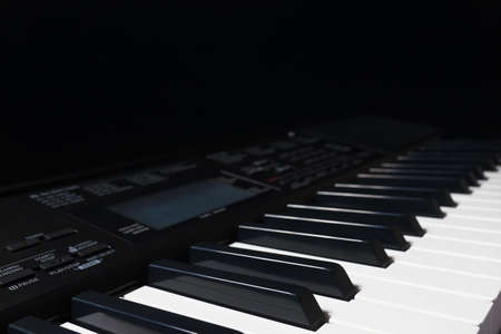 Keys of the synthesizer on a black background. Detail, selective focus. Stock Photo