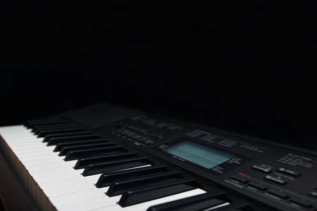 Keyboard of the electronic piano on a black background Stock Photo