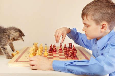 Little boy with a cute kitten plays chess.