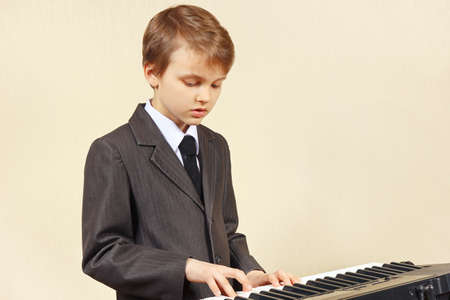 Little beginner musician in a suit playing the electronic synth