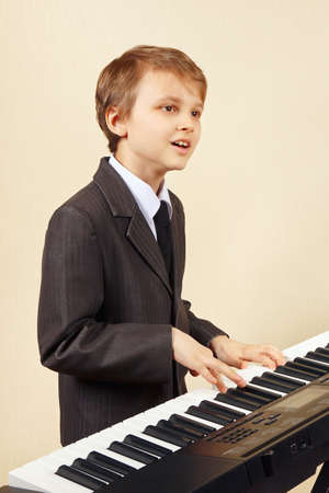 Young beginner musician in a suit playing the electronic synthesizer   Banque d'images