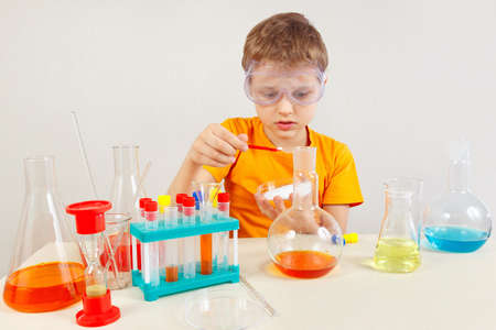 Little scientist in safety glasses studies chemical practice in the laboratory
